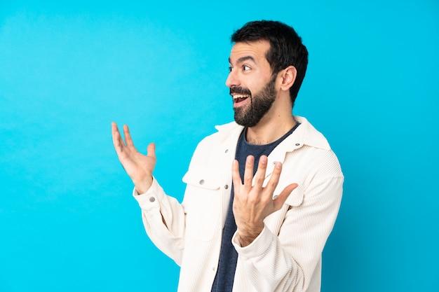 Jovem bonito com casaco de veludo branco sobre parede azul isolada com expressão facial de surpresa