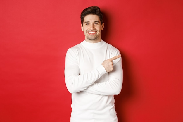 Jovem bonito com cerdas vestindo suéter branco apontando os dedos no canto superior direito e smi ...