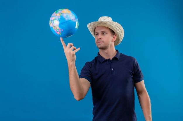 Jovem bonito com chapéu de verão girando o globo no dedo, parecendo confiante em pé sobre um fundo azul