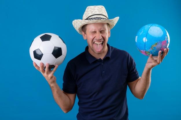 Jovem bonito com chapéu de verão segurando uma bola de futebol e um globo louco feliz gritando fascinado, mostrando a língua em pé sobre um fundo azul