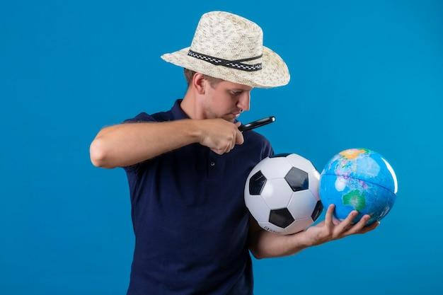 Jovem bonito com chapéu de verão segurando uma bola de futebol e um globo olhando através de uma lupa, intrigado em pé sobre um fundo azul
