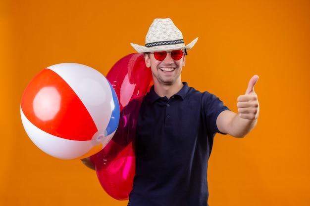 Jovem bonito com chapéu de verão usando óculos escuros vermelhos segurando uma bola inflável e um anel olhando para a câmera feliz e positivo sorrindo alegremente mostrando os polegares para cima em pé sobre o background laranja