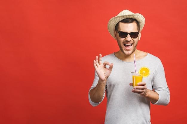 Jovem bonito com chapéu e óculos de sol bebendo suco de laranja fresco sobre fundo vermelho