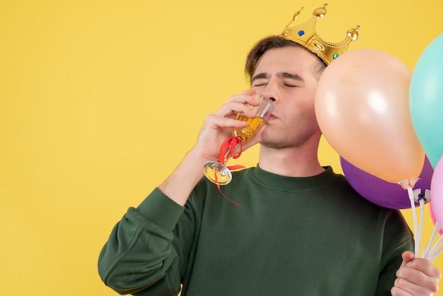 Jovem bonito com coroa segurando balões bebendo vinho em amarelo