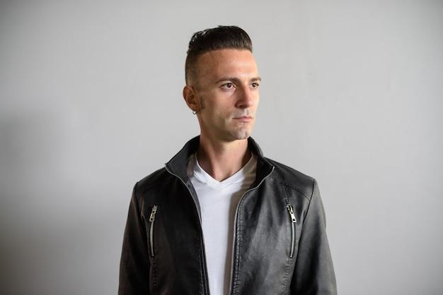 Jovem bonito com corte inferior vestindo uma jaqueta de couro preta enquanto pensa