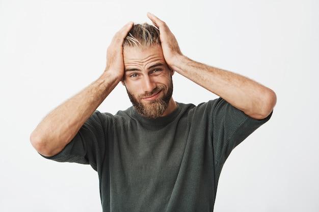Jovem bonito com expressão cansada por causa de dor de cabeça