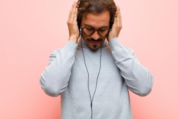 Jovem bonito com fones de ouvido contra parede plana-de-rosa
