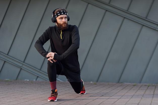 Jovem bonito com fones de ouvido, fazendo exercícios de alongamento e aquecimento antes de correr enquanto