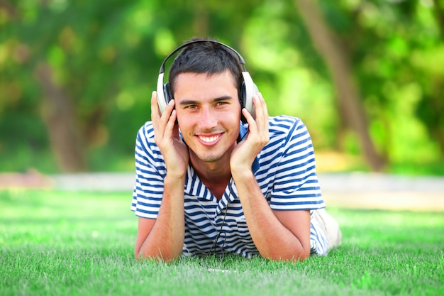 Jovem bonito com fones de ouvido na grama verde