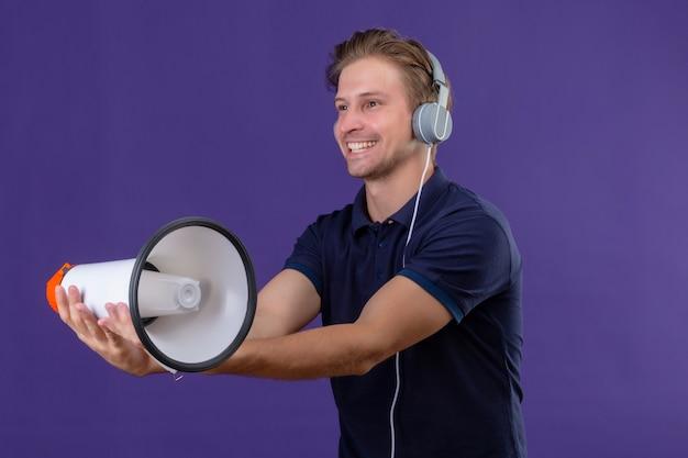 Jovem bonito com fones de ouvido segurando um megafone e um grande sorriso no rosto em pé sobre um fundo roxo