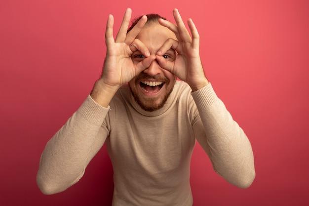 Jovem bonito com gola rulê bege olhando para a frente por entre os dedos fazendo gesto binocular sorrindo alegremente em pé sobre a parede rosa