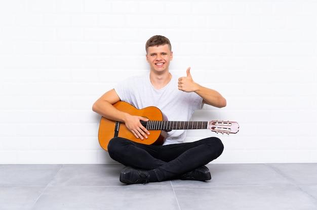 Jovem bonito com guitarra com polegares para cima, porque algo de bom aconteceu