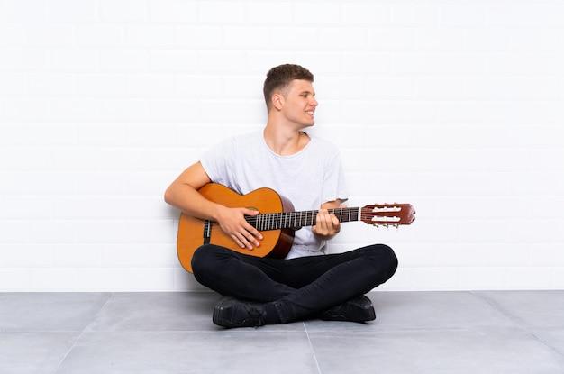 Jovem bonito com guitarra, olhando de lado