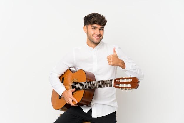 Jovem bonito com guitarra sobre branco isolado com polegares para cima, porque algo de bom aconteceu