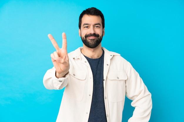 Jovem bonito com jaqueta de veludo branco sobre parede azul isolada, sorrindo e mostrando sinal de vitória