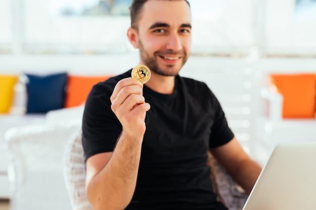 Jovem bonito com laptop mostrando bitcoin na câmera, sentado em um café nas férias de verão.