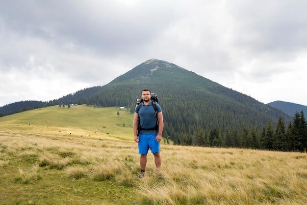 Jovem bonito com mochila em pé na montanha
