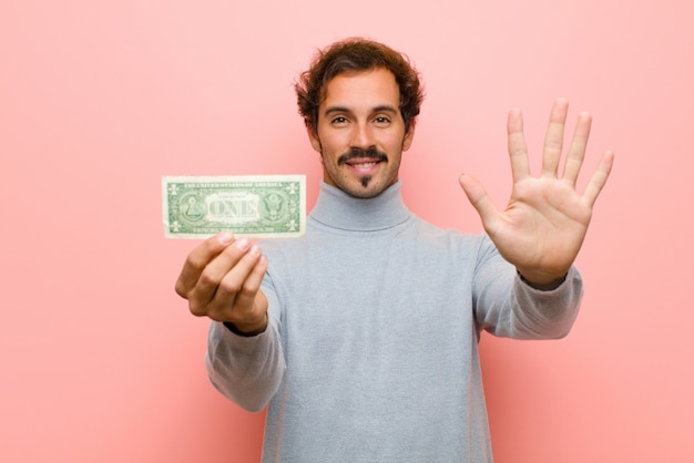 Jovem bonito com notas de dólar contra parede plana-de-rosa