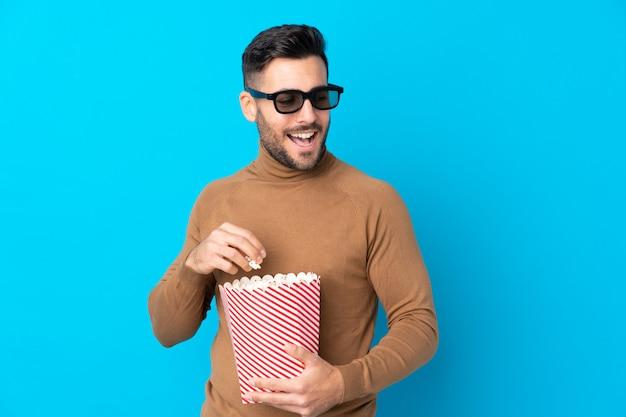 Jovem bonito com óculos 3d e segurando um grande balde de pipocas