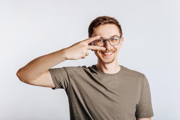 Jovem bonito com óculos fazendo o símbolo da paz em fundo cinza isolado