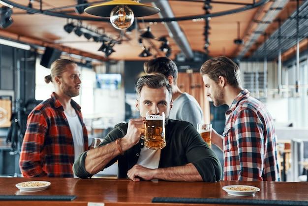 Jovem bonito com roupas casuais bebendo cerveja enquanto está com os amigos no bar