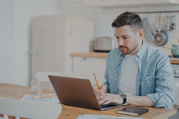 Jovem bonito com roupas casuais, usando o computador laptop em casa enquanto está sentado à mesa da cozinha e trabalhando remotamente em casa. conceito de educação freelance ou à distância