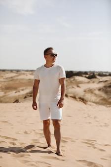 Jovem bonito com roupas leves e óculos escuros no deserto. conceito de relaxamento de liberdade