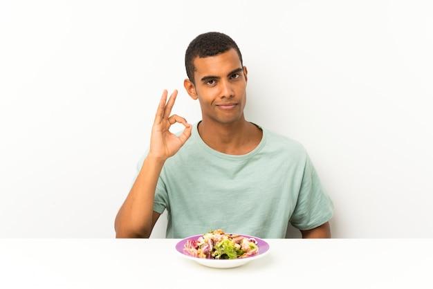 Jovem bonito com salada em uma mesa, mostrando um sinal de ok com os dedos
