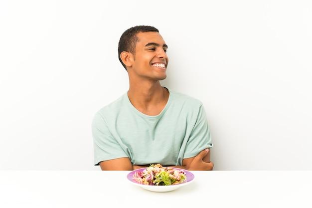 Jovem bonito com salada em uma mesa, olhando para o lado