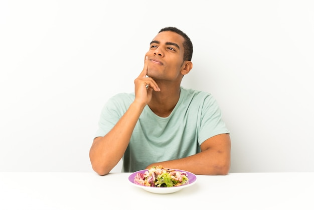 Jovem bonito com salada em uma mesa, pensando uma idéia