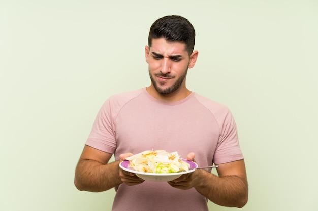 Jovem bonito com salada na parede verde