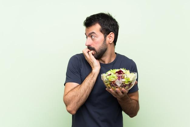 Jovem bonito com salada nervosa e assustada, colocando as mãos na boca