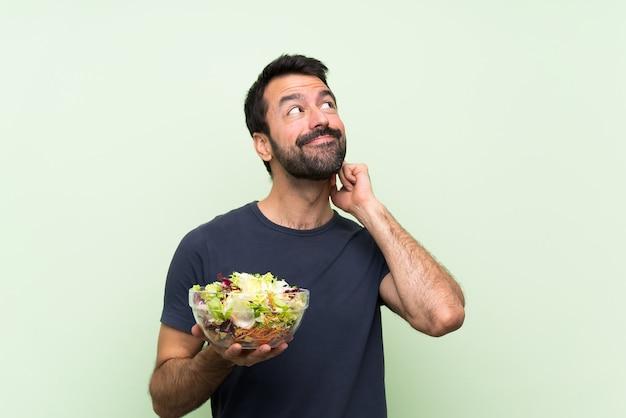 Jovem bonito com salada sobre parede verde isolada, pensando uma idéia