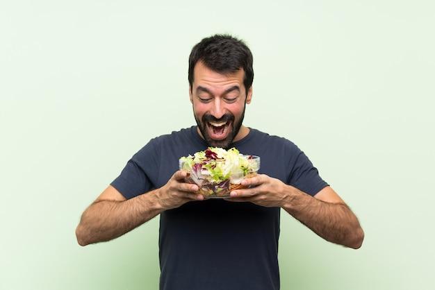 Jovem bonito com salada sobre parede verde isolada