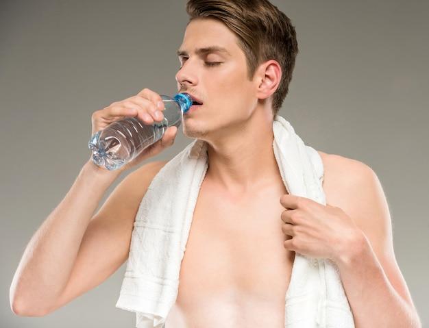 Jovem bonito com toalha nos ombros bebendo água