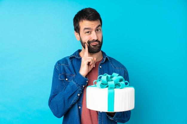Jovem bonito com um bolo grande sobre azul e olhando de frente