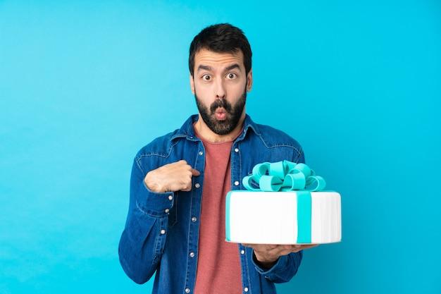 Jovem bonito com um bolo grande sobre parede azul isolada, apontando para si mesmo