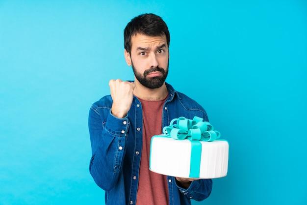 Jovem bonito com um bolo grande sobre parede azul isolada com gesto de raiva