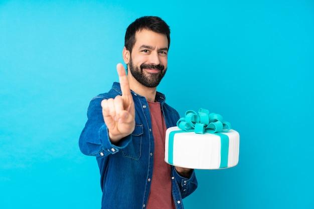 Jovem bonito com um bolo grande sobre parede azul isolada, mostrando e levantando um dedo