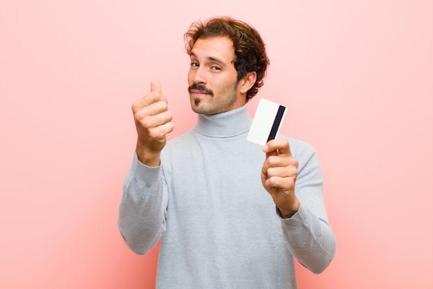 Jovem bonito com um cartão de crédito contra rosa plano