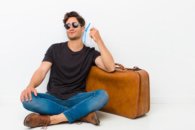 Jovem bonito com um cartão de embarque bilhetes sentado no chão em uma sala branca