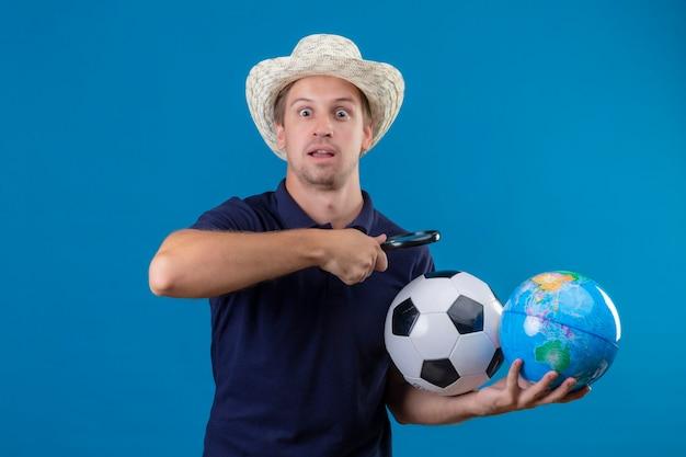 Jovem bonito com um chapéu de verão segurando uma bola de futebol e um globo indo olhar para o globo através da lupa, parecendo surpreso e espantado em pé sobre um fundo azul