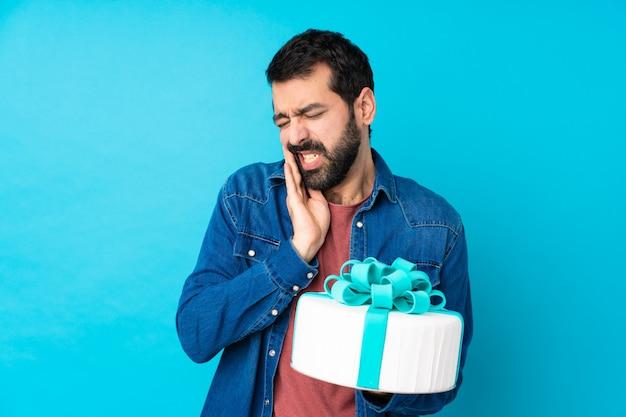 Jovem bonito com um grande bolo sobre azul com dor de dente