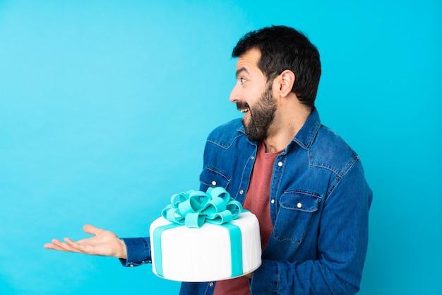 Jovem bonito com um grande bolo sobre azul com expressão facial de surpresa