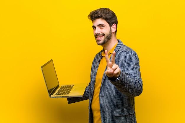 Jovem bonito com um laptop contra fundo laranja