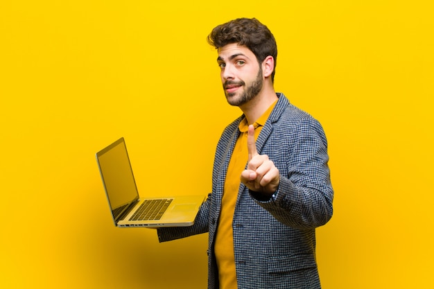 Jovem bonito com um laptop contra laranja