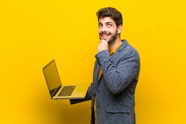 Jovem bonito com um laptop na laranja