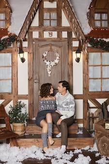 Jovem bonito com um suéter aconchegante e uma linda mulher com um vestido de malha aconchegante sentado na escada e ...