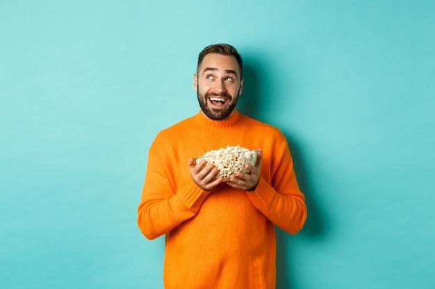 Jovem bonito com um suéter laranja, olhando pensativo no canto superior esquerdo, segurando pipoca