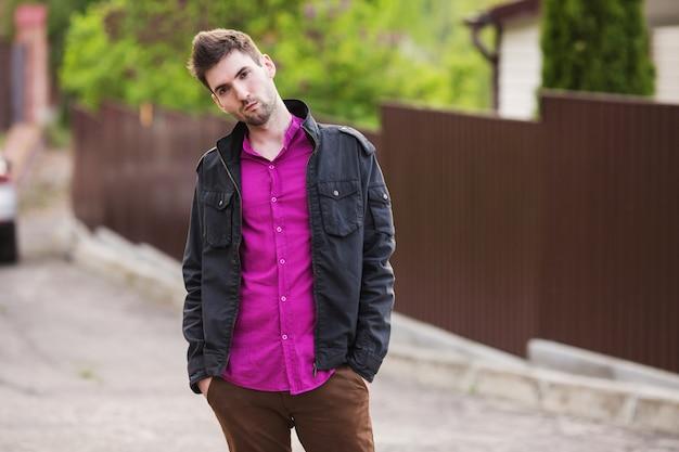 Jovem bonito com uma barba em uma camisa roxa e uma jaqueta preta na rua olha para a câmera